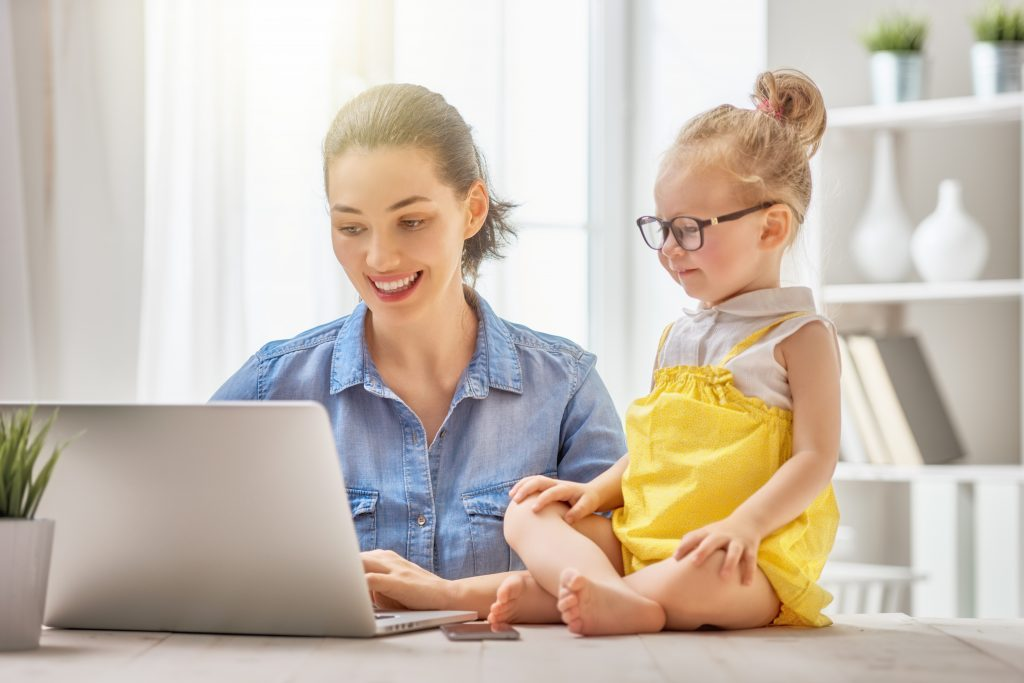 Mother and daughter working from home at a computer together