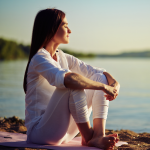 Brunette woman sitting on a yoga mat at the seaside