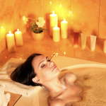 Woman taking a bubble bath with candles